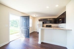 front door open lets light into kitchen and living room
