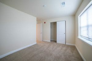 view of empty, carpeted bedroom and closet