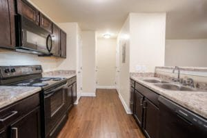 kitchen with electric stove and storage closets