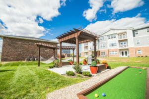 Bocce ball court and pergola with apartments in background