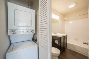 stacked washer and dryer next to bathroom