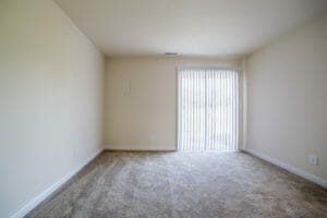carpeted, empty room with blinds over sliding door
